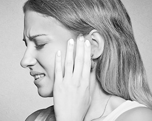 Woman holding her ear in pain.